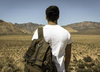 Uomo in montagna con zaino militare